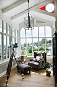 Armchair and telescope on tripod in period conservatory