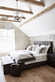 Attic bedroom with exposed beams and panelled walls
