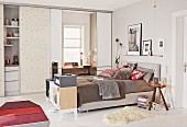 Boxspringbett, im Hintergrund Homeoffice und Küche mit Schiebetür abtrennbar, in Ein-Zimmer-Appartement