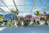 Glass vases of various flowers on table decorated for wedding on sunny day