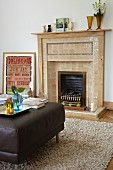 Open fireplace with tiled surround in traditional interior with modern ottoman
