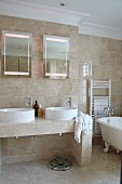 Bathroom with beige stone tiles, twin countertop sinks, two mirrors and free-standing, vintage-style bathtub
