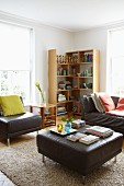 Gemütliches Wohnzimmer mit dunkelbraunen Ledermöbeln, Teppich und Holz-Eckregal zwischen hellen Sprossenfenstern