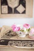 Pale pink ranunculus buds in vintage bowl on top of old magazines