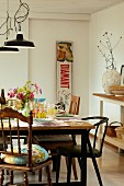 Set table, various chairs, vintage advertising panel and open shelving in country-house interior