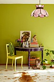 Ornaments on console table painted purple and yellow wooden chair against lime green wall in colourful, eclectic interior