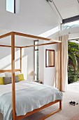 Wooden four-poster bed in bedroom with open French windows