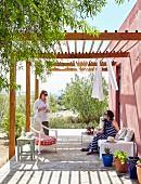 Zwei Frauen auf sonniger Terrasse unter Pergola vor altrosa getünchter Hauswand