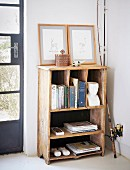 Books and framed pictures on vintage wooden shelves next to fishing rod leant against wall in corner