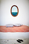 Black flip-flops in front of masonry bench covered in red and white throw below picture in oval wooden frame