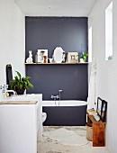 Floating shelf on dark grey wall and masonry washstand in minimalist bathroom