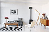 Coffee table on black-and-white-striped rug, chaise longue and white chair in minimalist living room