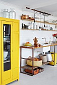 Yellow cabinet with glass door next to kitchen counter with wooden worksurface on metal frame