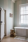 Ländliches Bad mit gedrechseltem Holzhocker neben freistehender Badewanne vor Sprossenfenster