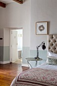Bed with button-tufted headboard, retro table lamp on bedside table and open bathroom door in background
