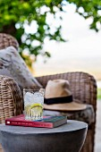 Refreshing drink on book on side table next to wicker armchair outdoors