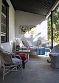White wicker furniture in comfortable seating area on traditional veranda