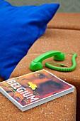 Neongrüner Telefonhörer und ein Buch auf dem Sofa