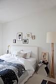 Decke mit Schafmotiven auf Doppelbett mit weißem Polsterkopfteil neben Nachttisch und Stehleuchte