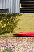 Red canoe leant against yellow brick courtyard wall