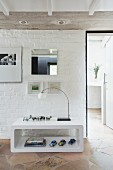 Modern shelving unit against white brick wall on stone floor