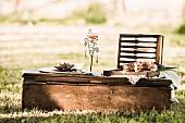Dekoratives Windlicht und offener Picknick-Besteckkasten auf Vintage Bodentisch im Freien