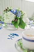 Table set with flowers in blue and white for afternoon coffee