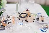 Kaffeekränzchen mit Gebäck auf Glasetagere auf Tischdecke mit blauem Stempeldruck