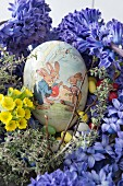 Hollow paper Easter egg in next of hyacinths, cowslips, thyme and sugar eggs