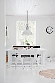 Weißes Esszimmer mit Lampe und Stühlen im Industriestil