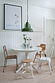 Round table and various chairs next to white wainscoting