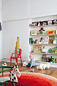 Toddler sitting on parquet floor below shelves of toys; retro rocking horse in foreground