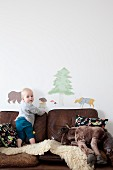 Toddler standing on sheepskin rug on brown leather sofa below animal wall-stickers