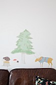 Animal and tree wall-stickers above leather sofa