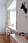 Schwarze Deko-Trophäe über Schränkchen mit Stofftier aus Stoffbällen und weißer Kinderhochstuhl vor Fensterbank