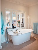 Free-standing bathroom with floor-mounted taps in front of interior window with open louvre shutters and view into bedroom