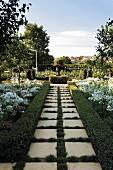 Geometrisch angelegter Garten mit gepflegter Buchshecke, weiß blühendem Agapanthus und Rondell mit bepflanzter Amphore