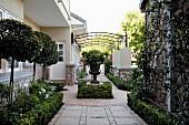Zentraler Blick auf bepflanzte Amphore auf Sockel vor elegantem Landhaus