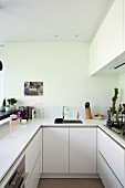 U-shaped galley kitchen with wall-mounted units and white worksurface
