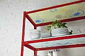 DIY kitchen shelves made from metal rails and wallpapered chipboard (detail)