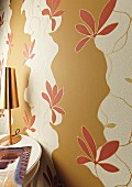 Wall decorated with cut-out sections of floral wallpaper over beige paint (detail)