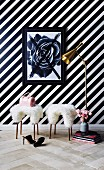 Two sheepskin-covered stools in front of black and white striped wallpaper in feminine interior