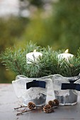 Two zinc buckets decorated with ribbon, spruce twigs and lit candles next to larch cones on surface