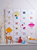 An advent calendar made from 24 envelopes stuck to cardboard with colourful number stickers with a deer figure in the foreground