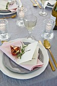 An elegant placecard menu with a a sprig of rosemary and a tree decoration