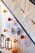 A banister decorated with paper stars and Christmas tree baubles