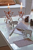 A 3D Christmas postcard with reindeer and star-shaped candles holders in the background