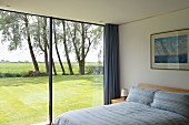 Modern bedroom with glass wall overlooking sunny lawn