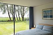 Modernes Schlafzimmer mit raumhoher Glasfront auf sonnigen Rasen