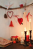 Christmas decorations hanging from branch above lit candles in candlesticks